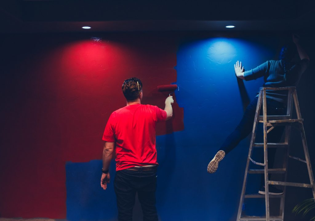 Two people applying different types of wall paint and finishes