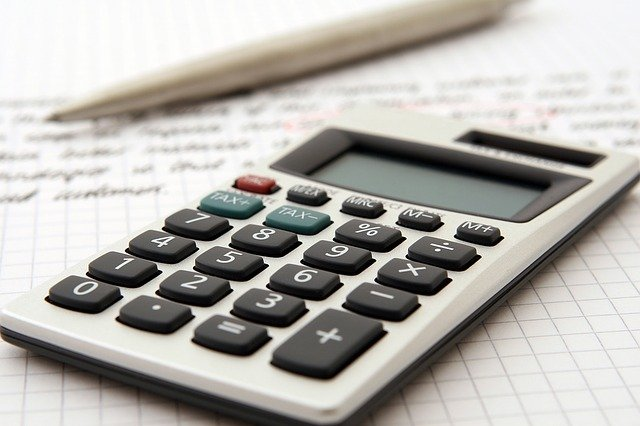 A calculator and a pen on a piece of paper